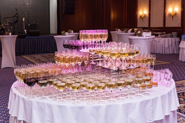 Champagne glasses of red and white wine on a white table.