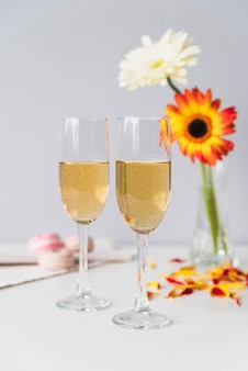 Champagne glasses surrounded by fowers
