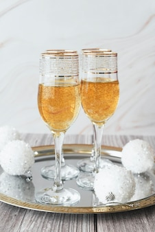 Champagne glasses with christmas balls on a tray