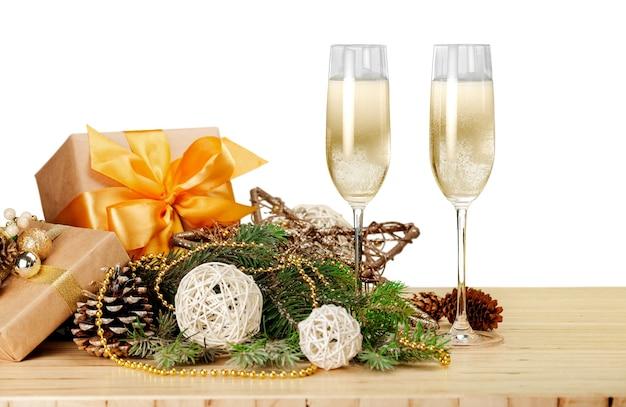 クリスマスの装飾とプレゼント付きのシャンパングラス