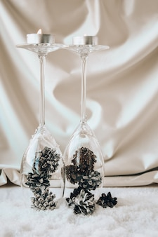 하얀 눈에 장식된 소나무 콘이 있는 샴페인 잔. 크리스마스 장식들. 새해 복 많이 받으세요. 공간을 복사합니다. 양초. diy 수제 장식. 제로 웨이스트 크리스마스
