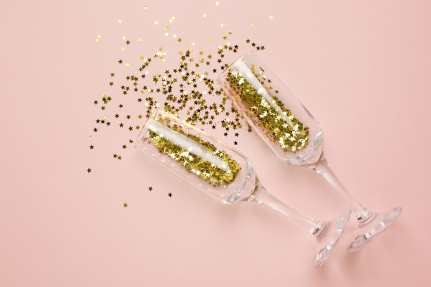 Champagne glasses with golden stars confetti on beige