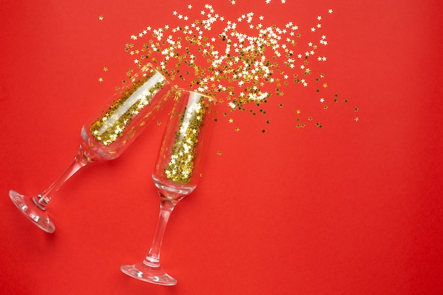 Champagne glasses with golden stars confetti, christmas and new year concept