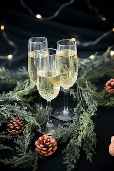 Champagne glasses with green branches on table