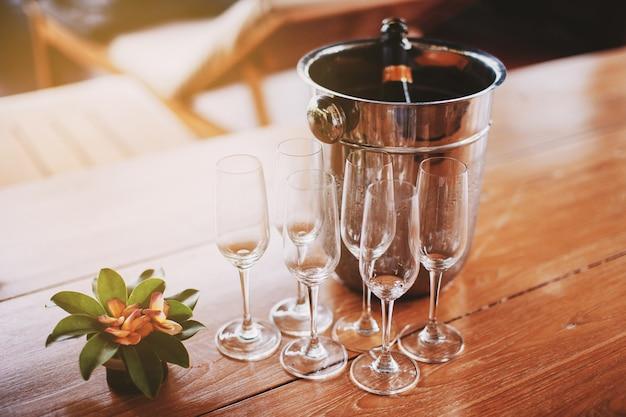 나무 테이블에 샴페인 병의 얼음 양동이와 샴페인 유리