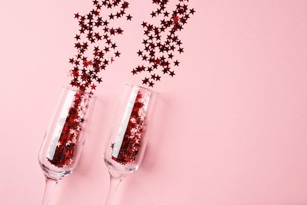 Бокалы для шампанского с красным конфетти на розовом фоне бумаги
