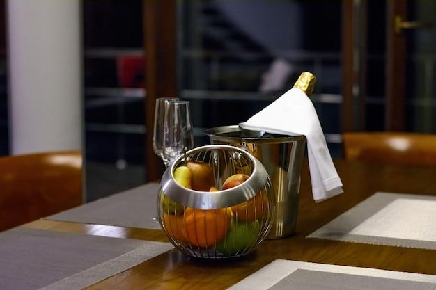 양동이에 샴페인과 테이블에 과일