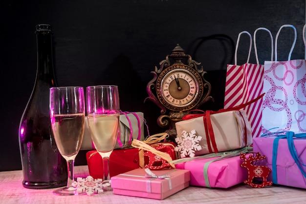화려한 크리스마스 선물 나무 테이블에 안경에 샴페인