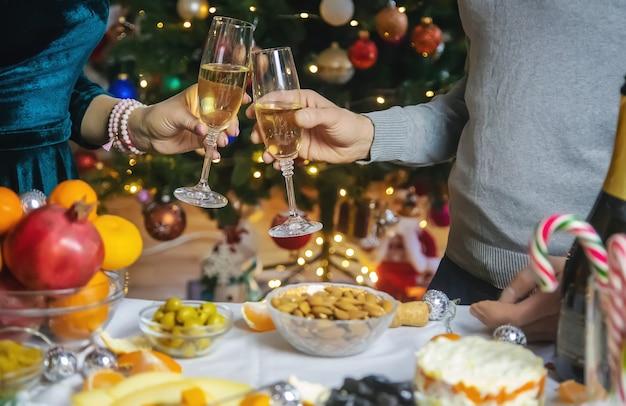 クリスマスツリーを背景にシャンパンを手に。人。セレクティブフォーカス。ホリデー。