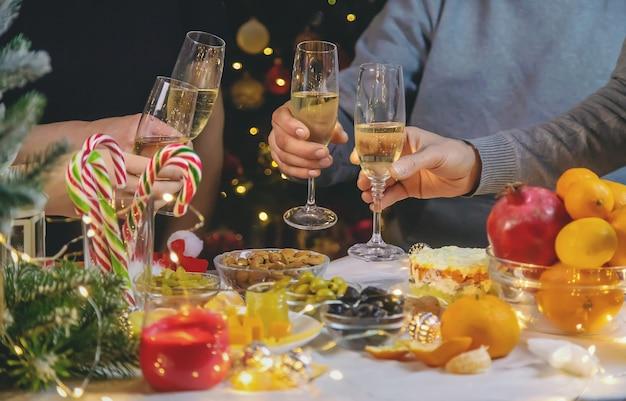 크리스마스 트리의 배경에 대해 손에 샴페인. 사람들. 선택적 초점입니다. 휴일.