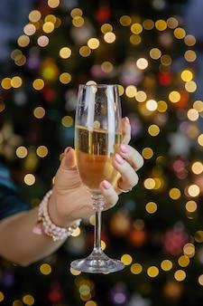 クリスマスツリーを背景にシャンパンを手に。セレクティブフォーカス。ホリデー。