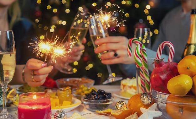 クリスマスツリーに対して手にシャンパン