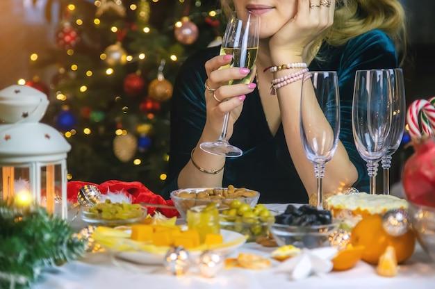 一人でクリスマスツリーの背景にシャンパンを手に。セレクティブフォーカス。ホリデー。