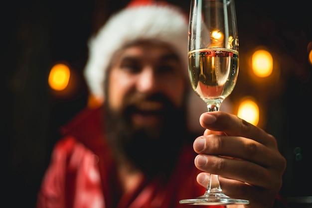 シャンパンを手にお祝いの幸せな男性。サンタクロースはメリークリスマスを願っています。サンタはシャンパンを手に持っています。