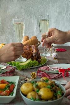 手にシャンパン。クリスマステーブル。新年。