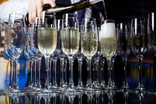 ガラスの透明なテーブルの上に立つ空のグラスにシャンパンを注ぐ