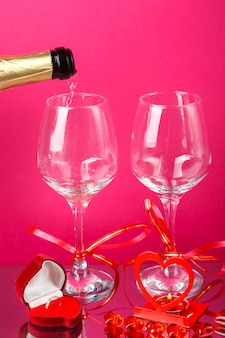 Champagne is poured into glasses on a pink background next to a heart-shaped box with a ring. vertical photo