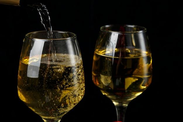 Шампанское разливается в бокалы без ножек на черном фоне. горизонтальное фото