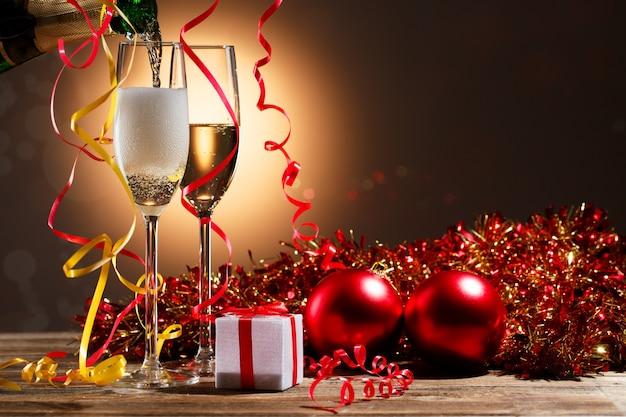 Шампанское, льющееся из бутылки в бокалы и рождественские украшения