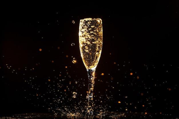 黒の背景にグラスに注ぐシャンパン