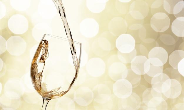 Шампанское наливается в бокал на размытом фоне света боке
