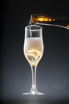 Champagne pouring into glass on black background