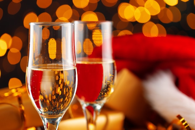Champagne and santa claus hat on blurred garland background front view