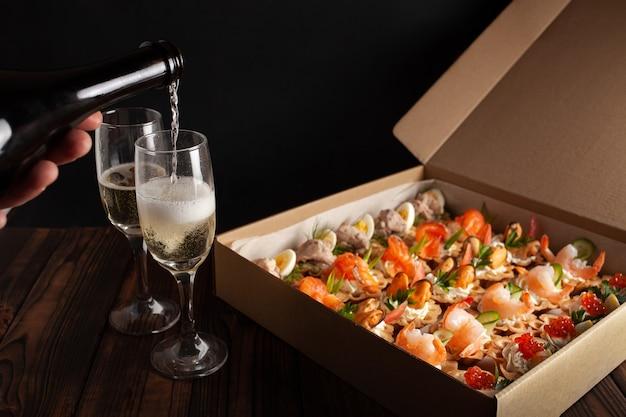 シャンパン、タルト、シーフードサラダ。食品の段ボール箱。休日、パーティー、家族の夕食への贈り物。ケータリング。