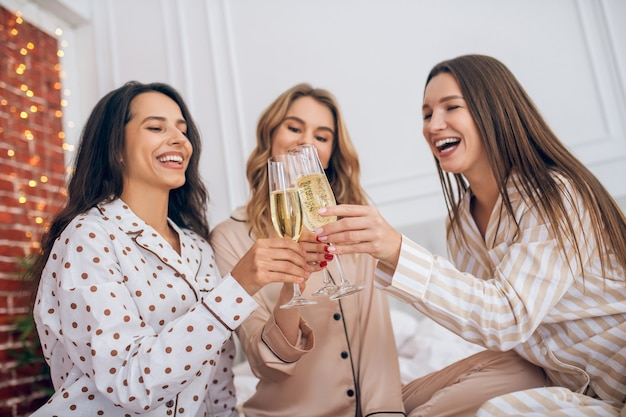 Champagne. three young girls having pajama party and drinking champagne