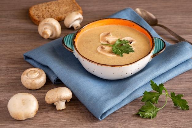 세라믹 접시에 샴 피뇽 크림 수프 나무 테이블에 빵 샴 피뇽 파슬리 비타민 항산화 제와 섬유질이 풍부한 건강 식품