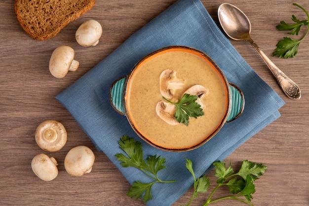 세라믹 접시에 샴 피뇽 크림 스프, 나무 테이블 위에 샴 피뇽 파슬리, 비타민 산화 방지제와 섬유질이 풍부한