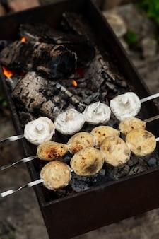 Грибы шампиньоны обжаривают на шпажках на мангале. пикник на природе. крупный план. вертикальный.