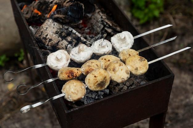 Грибы шампиньоны обжаривают на шпажках на мангале. пикник на природе. крупный план.