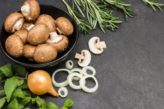 Champignon mushrooms in black bowl, chopped onions and mushrooms with sprigs of mint and rosemary