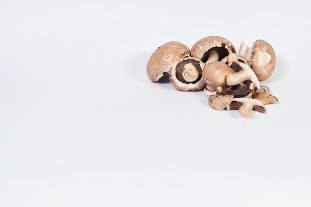 Грибы шампиньоны коричневой разновидности в правом верхнем углу на белой поверхности с местом для записи.