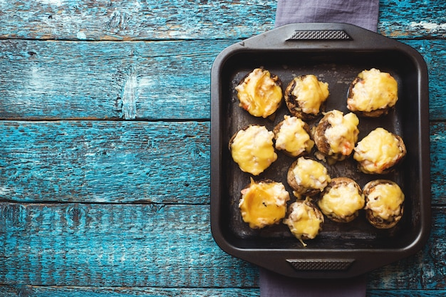 Champignon mushrooms stuffed with cheese, chicken and herbs baked in oven