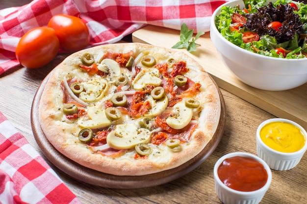 木製のテーブルにサラダ、トマト、ソースのシャンピニオンピザ