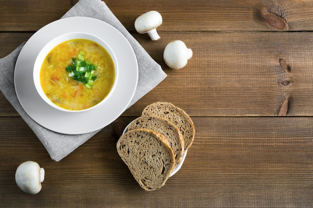 Суп из шампиньонов в белой миске на салфетке с грибным хлебом на деревянном коричневом фоне с копией пространства