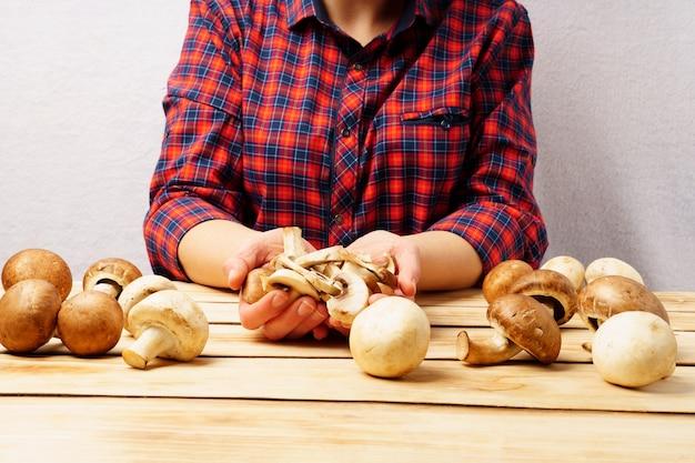 손에 champignons. 빨간 체크 무늬 셔츠를 입은 소녀는 나무 배경에 그녀의 손에 신선한 버섯을 보유하고 있습니다.
