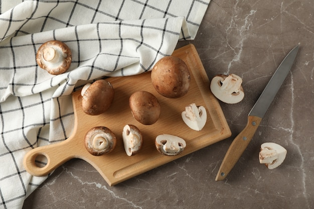 Champignons, knife, board and towel on grey, top view