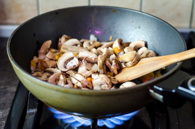 Champignons with onions are fried in pan, fire.