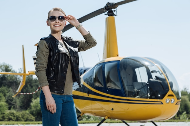 Champing at bit. beautiful young female pilot adjusting her glasses and posing near a helicopter while waiting for the start of the flight