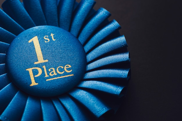 Champion 1st place blue rosette with gold text on black background