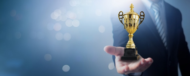 챔피언과 성공 우승자 개념, 사업가 리더십 트로피와 소프트 블루와 나뭇잎에 비즈니스 챔피언 컵을 들고