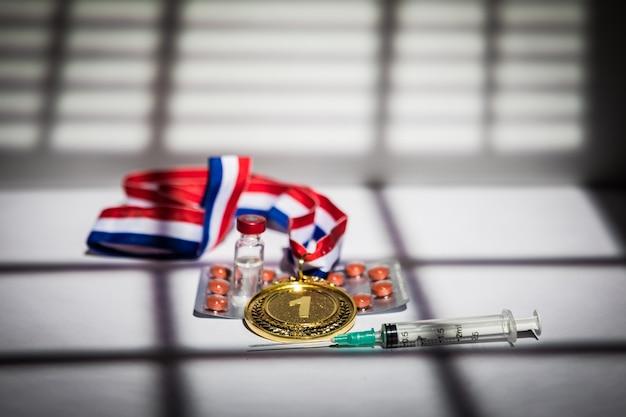 Золотая медаль чемпиона, шприц с допинговым веществом, таблетка с таблеткой и флакон с запрещенным веществом с подсветкой и тенями занавеса, проникающего через окно. концепция спорта и допинга