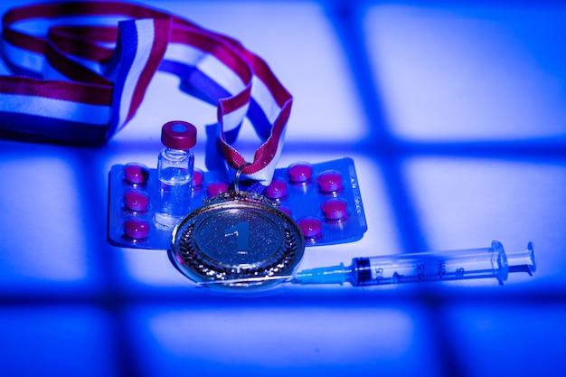 Золотая медаль чемпиона, шприц с допингом, таблетка и флакон с запрещенным веществом с огнями и тенями занавеса, проникающего через окно в ночное время. концепция спорта и допинга