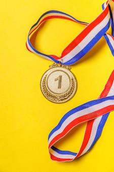 Золотая медаль чемпиона, изолированные на желтом фоне