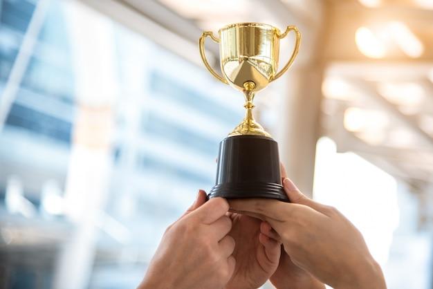 Золотой трофей победителя со спортивными руками на спортивном стадионе