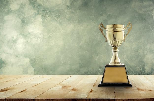 챔피언 황금 트로피 빈티지 벽 배경으로 나무 테이블에 배치