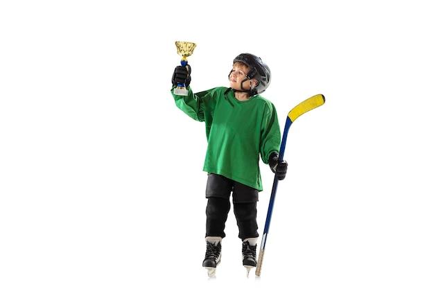 챔피언. 얼음 코트와 흰 벽에 막대기로 작은 하키 선수. sportsboy 입고 장비 및 헬멧 훈련. 스포츠, 건강한 라이프 스타일, 운동, 운동, 행동의 개념.